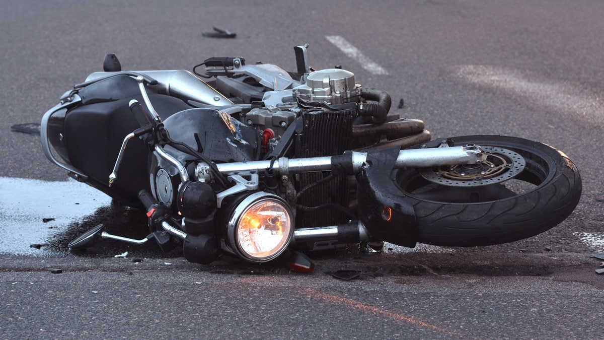 A crashed motorcycle laying on the road.